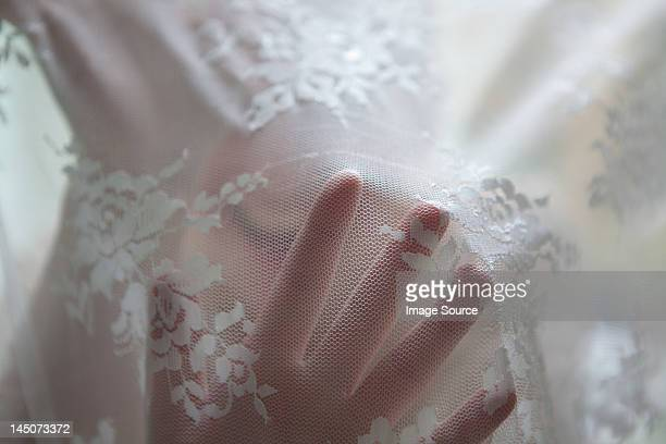 Hand of woman behind lace curtain