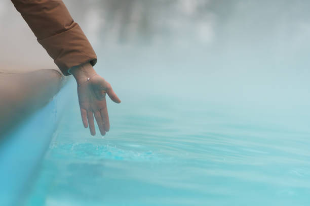 Hand Of Woman Checking Temperature Of Water In Open Swimming Pool In Winter. Thermal Spa Outdoors.