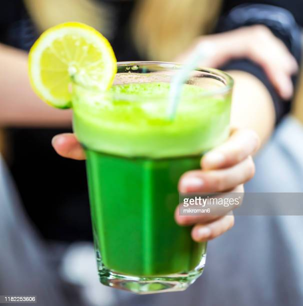 hand of woman holding a glass of green smoothie - stoffwechsel entgiftung stock-fotos und bilder