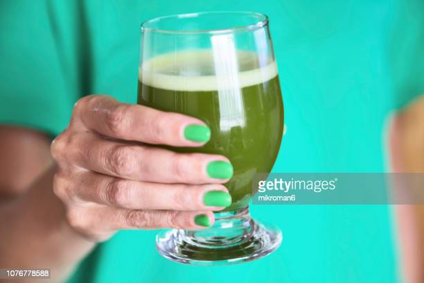 Hand of woman holding a glass of Japanese powdered green tea