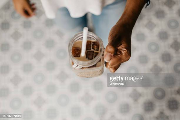 hand of woman holding glass of iced coffee i - iced coffee stock pictures, royalty-free photos & images