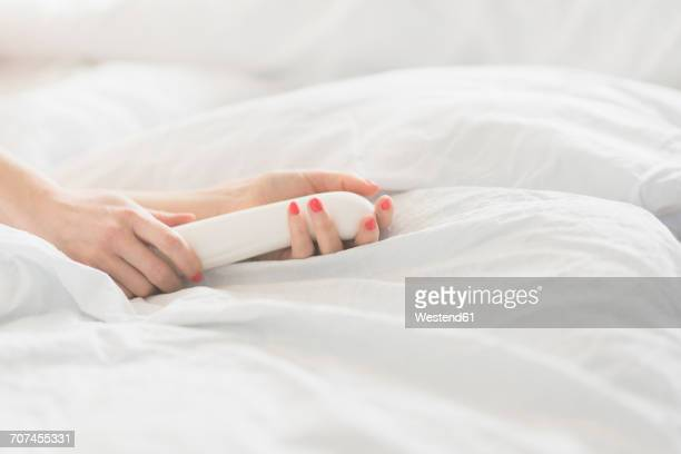 hand of woman holding sex toy in bed - erotiek stockfoto's en -beelden