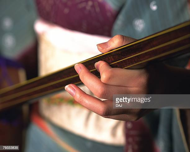 a hand of woman in kimono playing shamisen, high angle view, close up, differential focus - vangen imagens e fotografias de stock