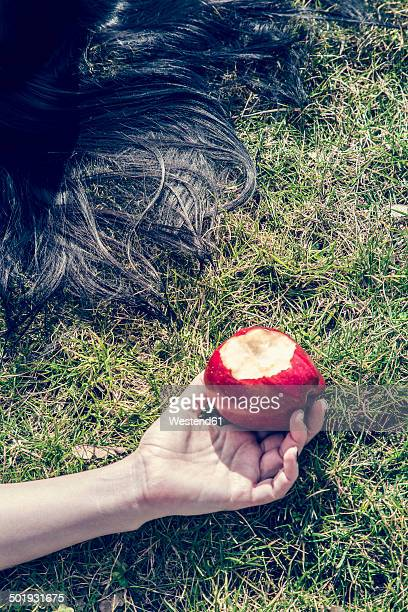 Hand of woman lying on grass holding bitten red apple