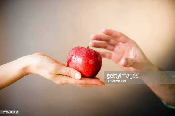 Hand of woman offering red apple to man