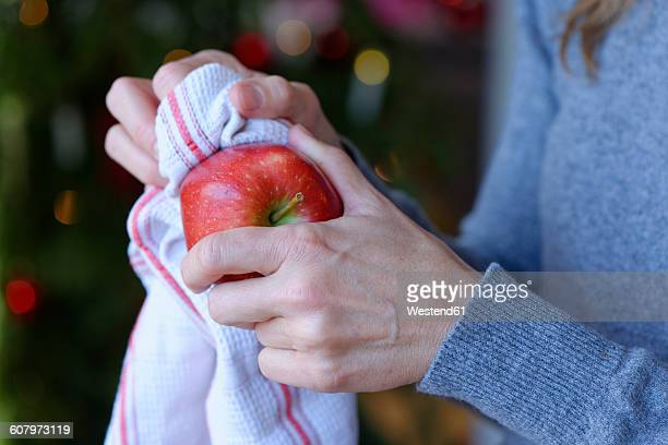 Hand of woman polishing Christmas apple with kitchen towel, close-up
