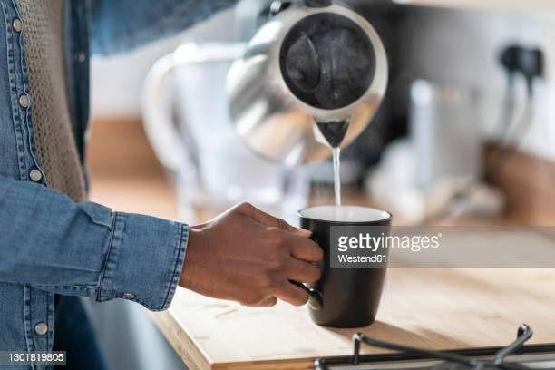 hand of woman pouring water from kettle into mug in kitchen - preparation stock pictures, royalty-free photos & images