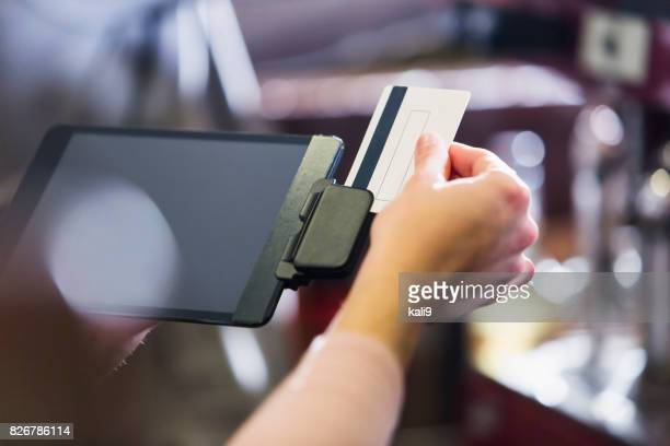 hand of woman sliding credit card through reader - gift card imagens e fotografias de stock