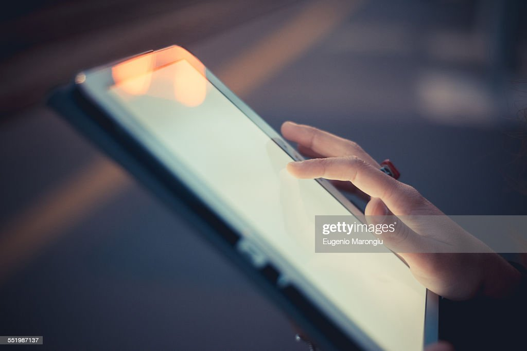 Hand of woman using digital tablet touchscreen at dusk : Stock Photo