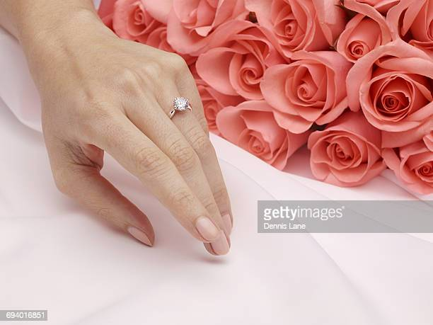 Hand of woman wearing engagement ring near roses