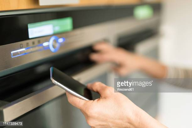 hand of woman with smartphone checking oven in kitchen at her smart home - appliance stock pictures, royalty-free photos & images