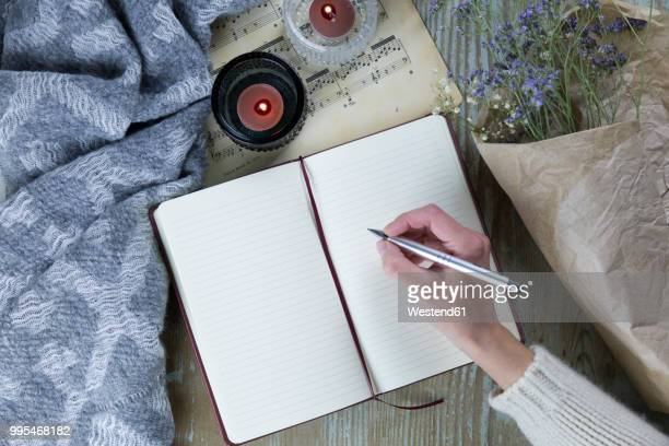 hand of woman writing in notebook - hygge stock pictures, royalty-free photos & images