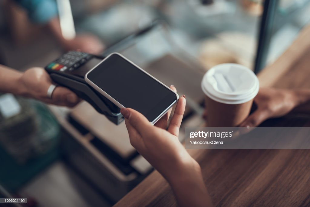 Hand of young lady placing smartphone on credit card payment machine : Stock Photo