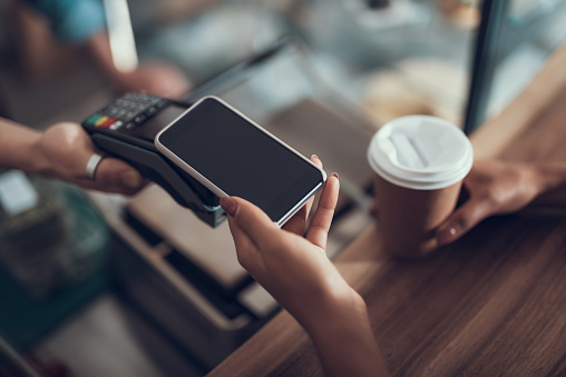 Hand of young lady placing smartphone on credit card payment machine 1096021192
