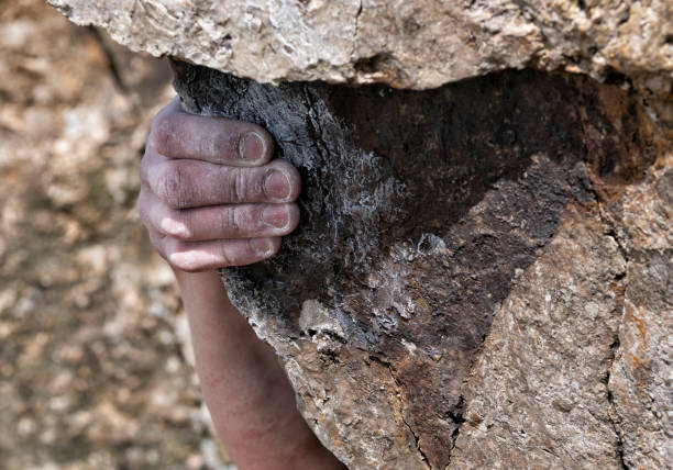 Hand of young man climbing boulder