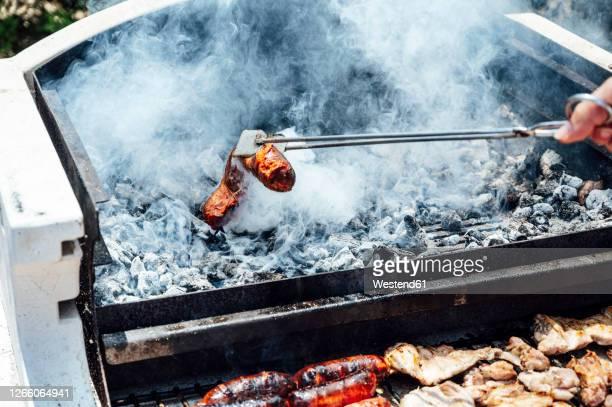 hand of young man holding meat with serving tongs over barbecue grill in yard - ember stock pictures, royalty-free photos & images