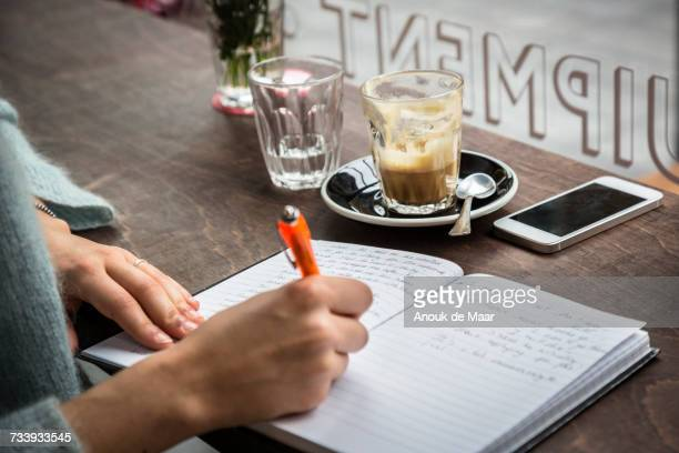 Hand of young woman at cafe window seat writing notes