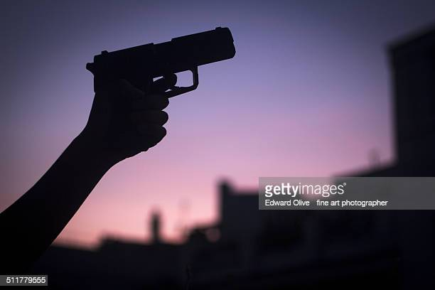 Hand of young woman holding pistol revolver gun