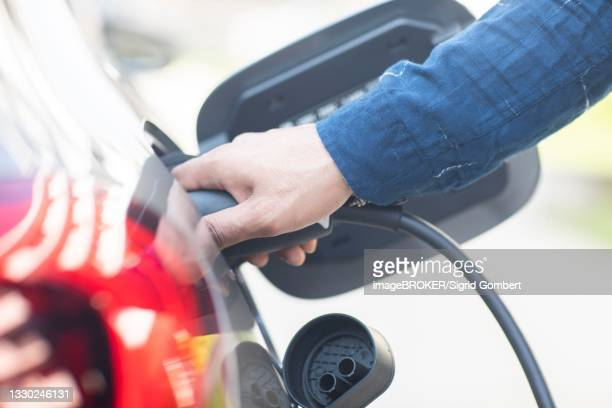 hand on an electric car charging cable at the car, freiburg, baden-wuerttemberg, germany - sigrid gombert stock-fotos und bilder