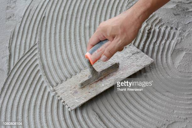 hand on be bound with cement , do cement work, apply cement (over a surface) - wall building feature stock pictures, royalty-free photos & images