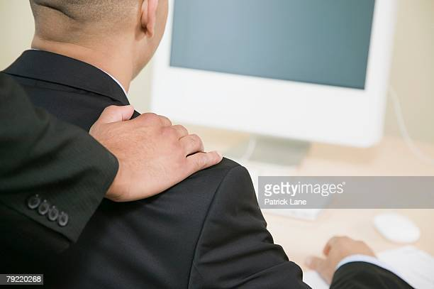 Hand on co-worker's shoulder