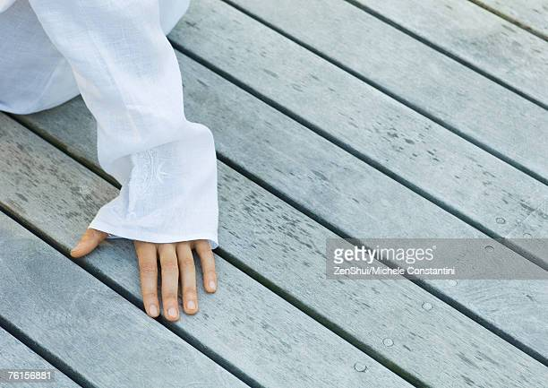 Hand on decking, cropped view