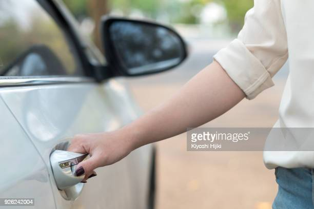 Hand on door handle. Close-up of female hand open a car door
