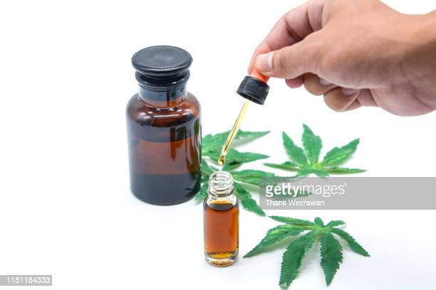 hand on drop cannabis oil on white background - cbd oil stock pictures, royalty-free photos & images