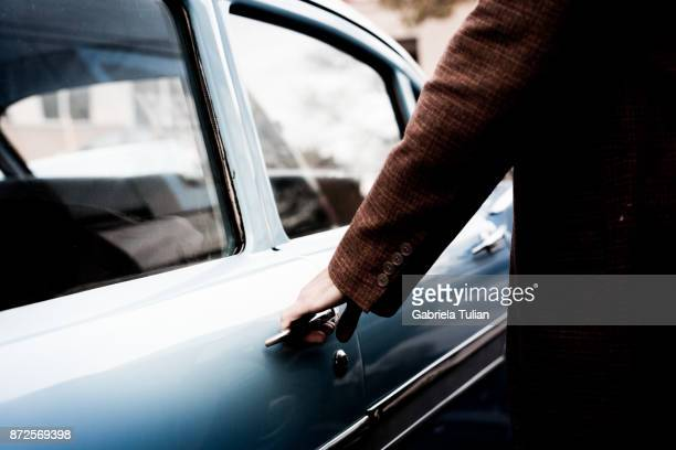 Hand on handle. Close-up of man hand opening a vintage car door