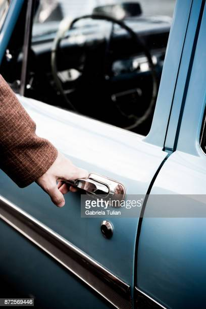 hand on handle. close-up of man hand opening a vintage car door - handle stock pictures, royalty-free photos & images