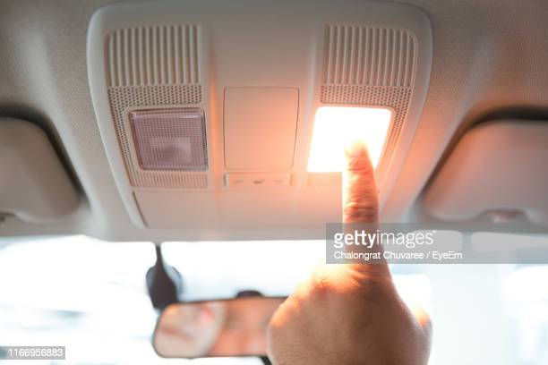 Hand On Man Touching Light On Dashboard In Car