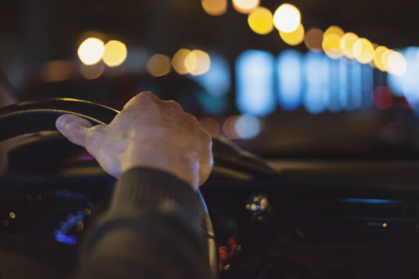 hand on steering wheel - car at night stock pictures, royalty-free photos & images
