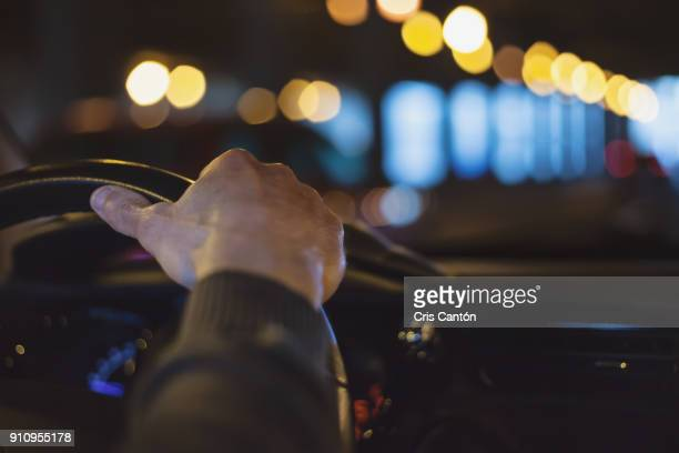 hand on steering wheel - conducir fotografías e imágenes de stock