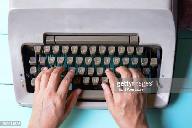 hand on type old style typewriter - schriftsteller stock-fotos und bilder
