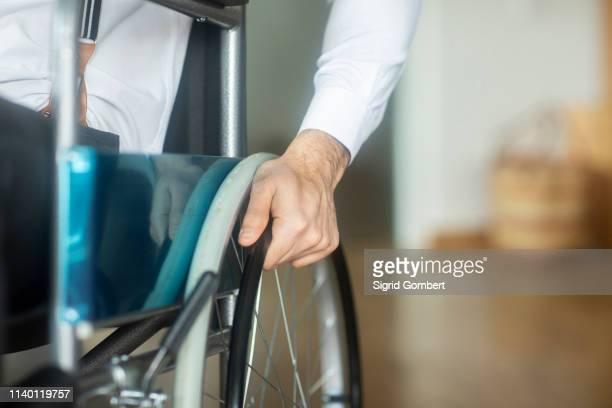 hand on wheel of wheelchair - sigrid gombert stock-fotos und bilder