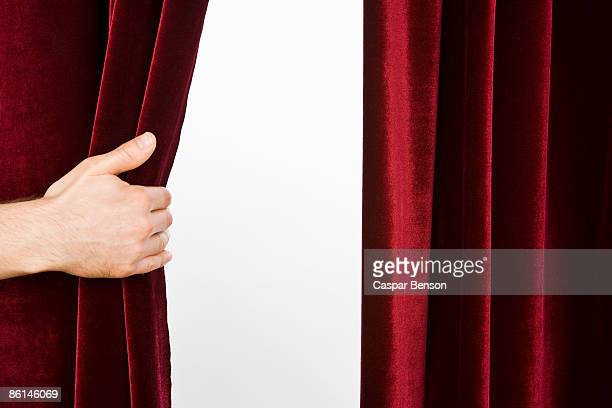 A hand opening a red velvet curtain