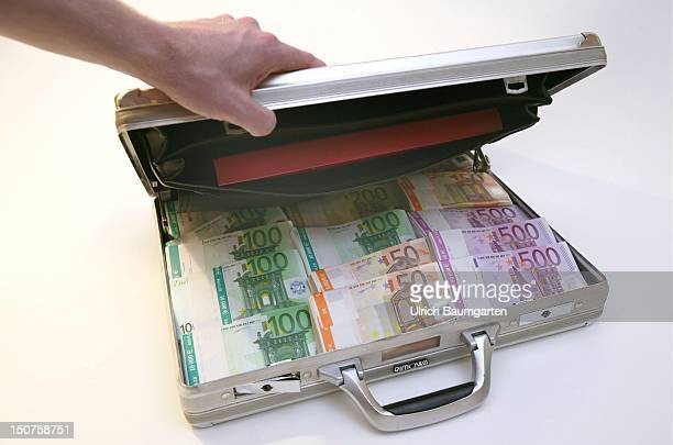 Hand opening a suitcase full with Euro notes Symbolic picture money laundering illegal money bribery