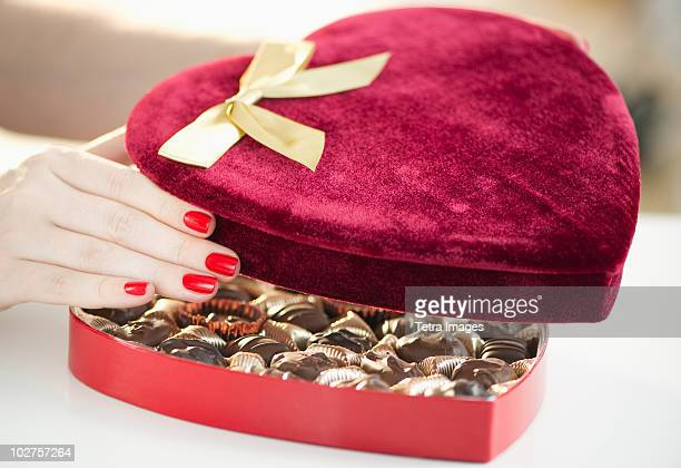 Hand opening a velvet heart shaped box of chocolates