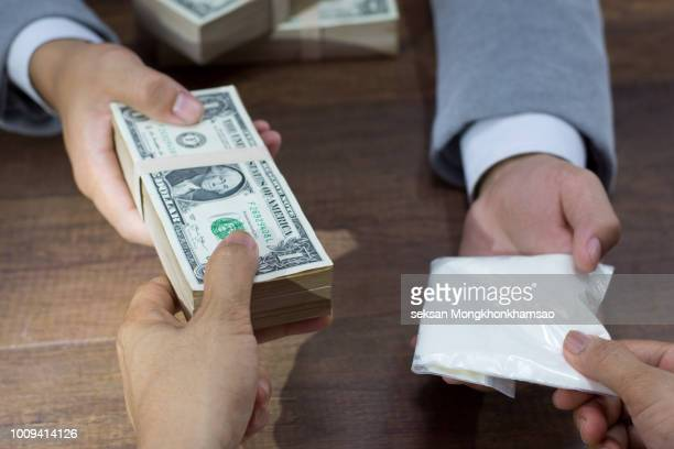 Hand out to send money to buy the drugs, many banknote and drugs on wooden table, concept about the drug problem, drug addiction and has been trading.