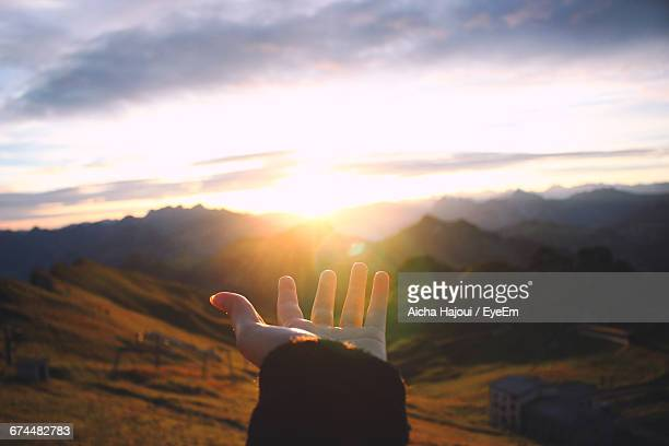 hand outstretched towards scenic view of mountains - geloof stockfoto's en -beelden