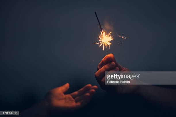 hand outstretched towards sparkler