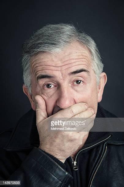 Hand over mouth surprised mature man portrait