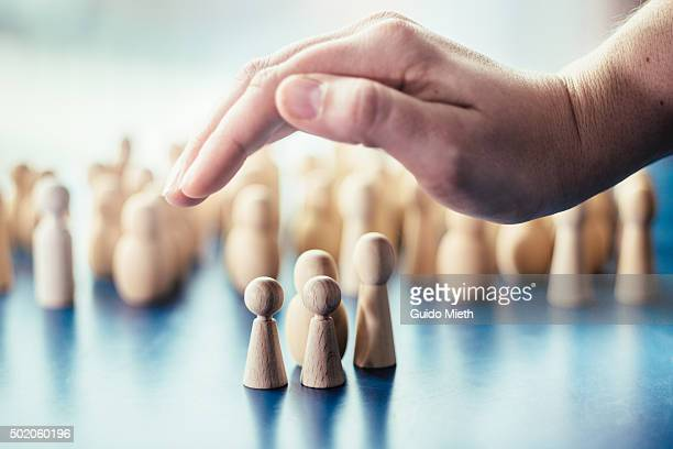 hand over symbolic pawn family. - protection stock pictures, royalty-free photos & images