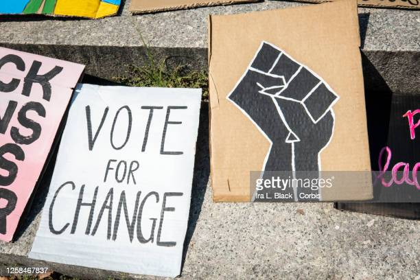 Hand painted and crafted signs which include one that has a back power fist and another that says Vote for Change lay on the ground at Cadman Plaza...