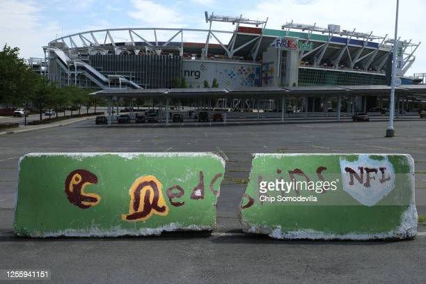Hand painted concrete barriers stand in the parking lot of FedEx Field, home of the NFL's Washington Redskins team July 13, 2020 in Landover,...