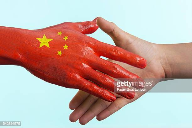 Hand painted flag of China doing a handshake