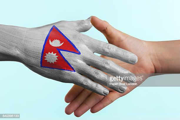 hand painted flag of nepal doing a handshake - nepali flag stock pictures, royalty-free photos & images