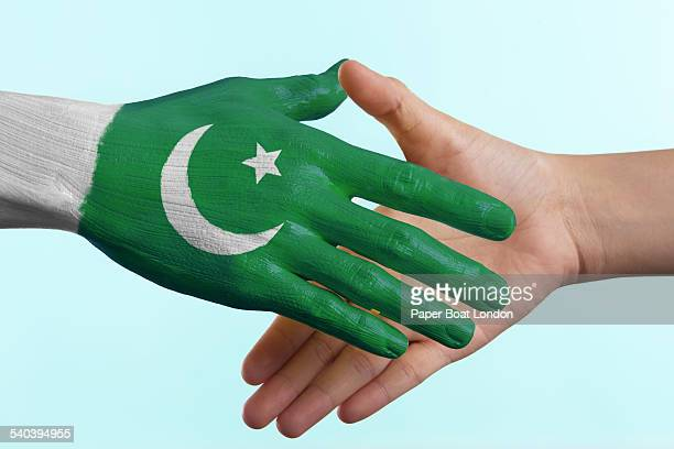 hand painted flag of pakistan doing a handshake - pakistani flag stock photos and pictures