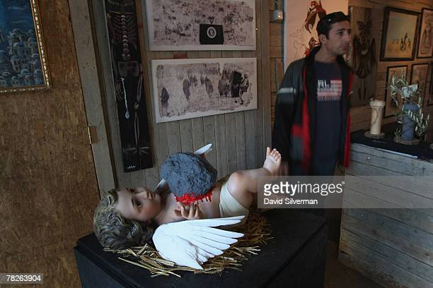 A hand painted sculpture by elusive British graffiti artist Banksy called The Death Of Christianity shows a cherub bleeding from a wound made by a...