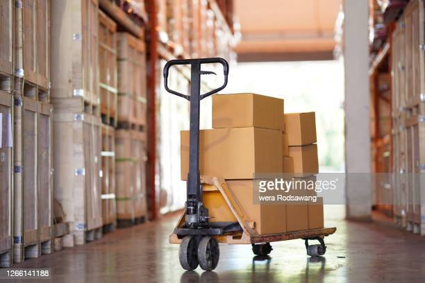 hand pallet truck carrying empty cardboard box in warehouse distribution - sack barrow stock pictures, royalty-free photos & images